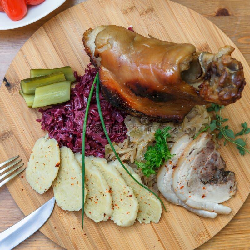 Pieczonej wieprzowiny knykieć słuzyć z gotowaną kapustą, chlebem, horseradish i musztardą, widok od above zdjęcia royalty free
