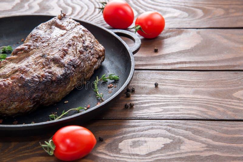Pieczonej wołowiny stek kropiący z ziele i pikantność na czarnej żelaznej smaży niecce na drewnianym stole z czereśniowymi pomido fotografia stock
