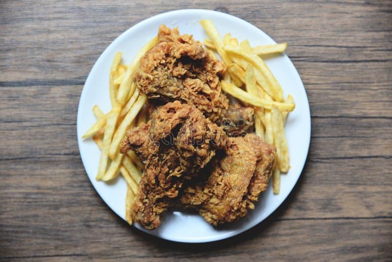 Pieczony kurczak crispy na bielu talerzu z francuzem smaży na łomotać stół fotografia royalty free