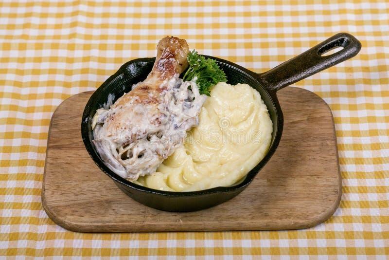 Pieczony kurczak noga z pieczarkowym kumberlandem, papryką i czosnkiem z puree ziemniaczane jako, masło i garnirunek, słuzyć w mi obraz stock
