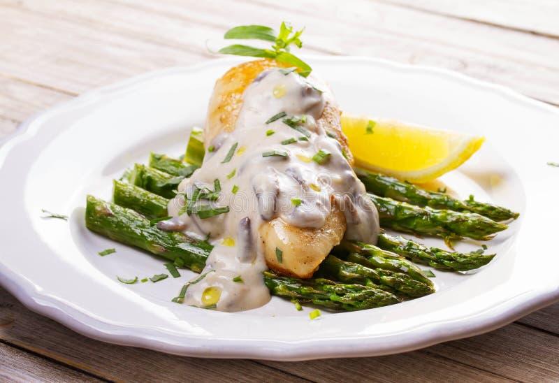 Pieczony kurczak pierś na asparagusie z estragonowym i pieczarkowym kumberlandem zdjęcie stock