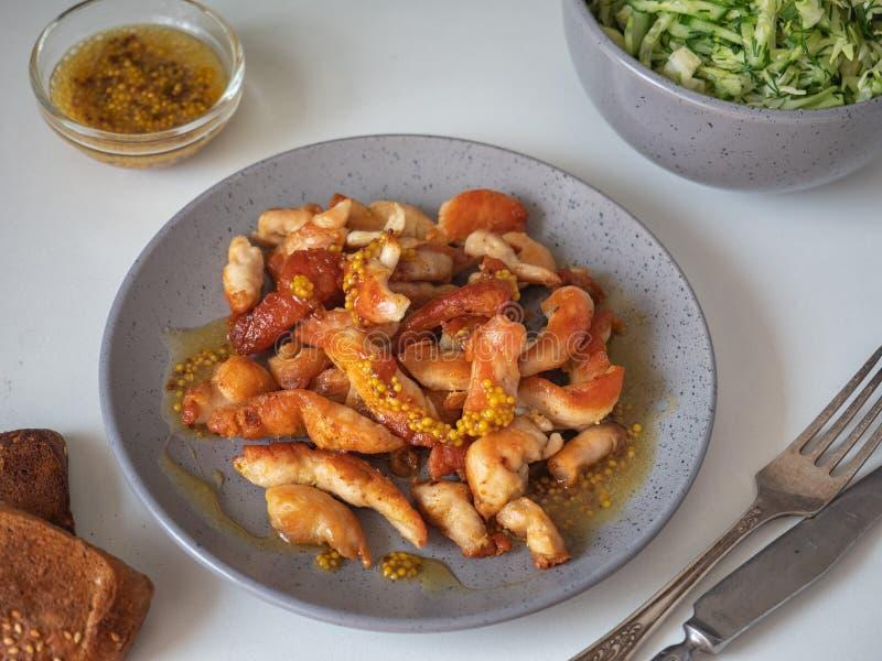 Pieczony kurczak pierś pokrajać w małych kawałkach na szarość talerzu, strzale i cutlery na białym tle, przy zamkniętym pasmem obrazy stock