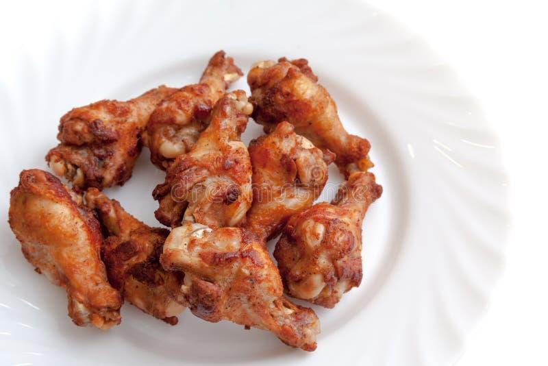 Pieczony kurczak uskrzydla gotowego słuzyć na półkowym białym backgroun obraz royalty free