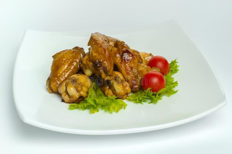Pieczony kurczak uskrzydla z pomidorami i sałatą na białym talerzu zdjęcia stock