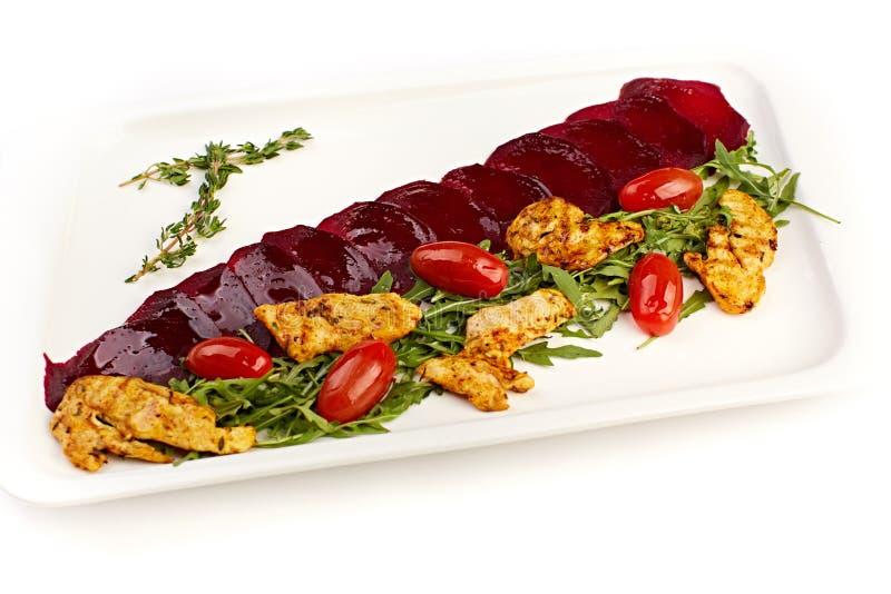 Pieczony kurczak z beetroot, pomidorami i ziele na bielu talerzu, obrazy stock