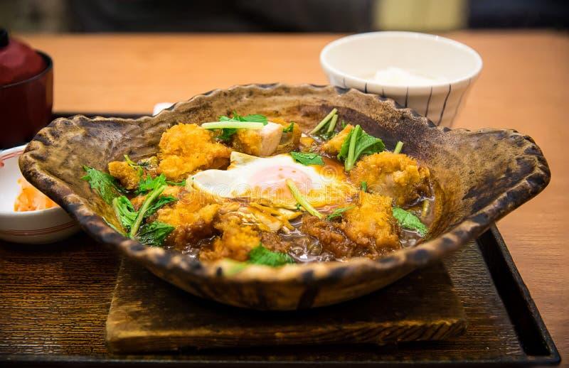 pieczony kurczak z jajkiem w miso polewki serw na gorącym kamiennym pucharze obraz royalty free