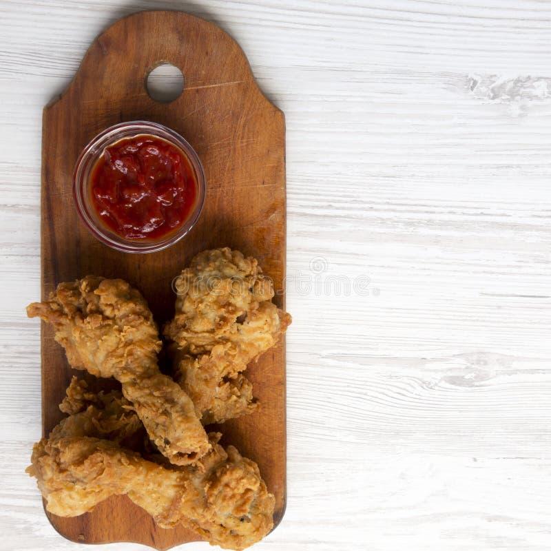 Pieczonych kurczaków drumsticks z ketchupem na drewnianej desce nad białą drewnianą powierzchnią, odgórny widok Koszt stały, mies obraz stock