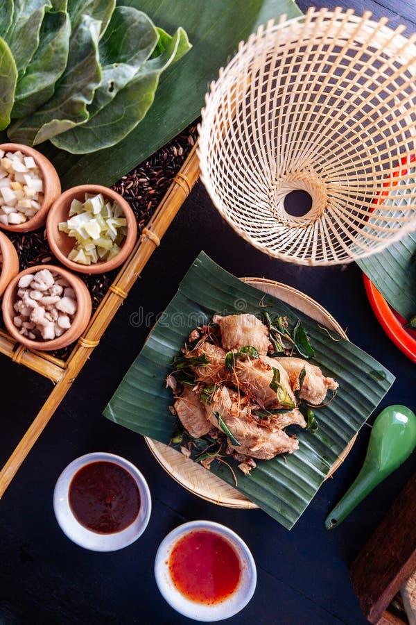 Pieczonych kurczaków skrzydła w Tajlandzkim northeastern stylu z czosnku i kaffir wapna liśćmi słuzyć na bananowym liściu zdjęcia stock