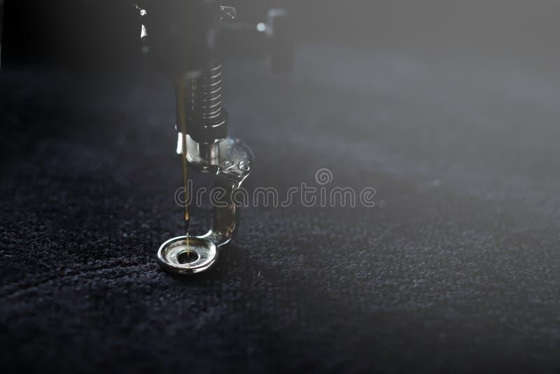Pied d'aiguille et de broderie d'une machine à coudre moderne piquant avec le fil d'or sur le tissu mou noir image libre de droits