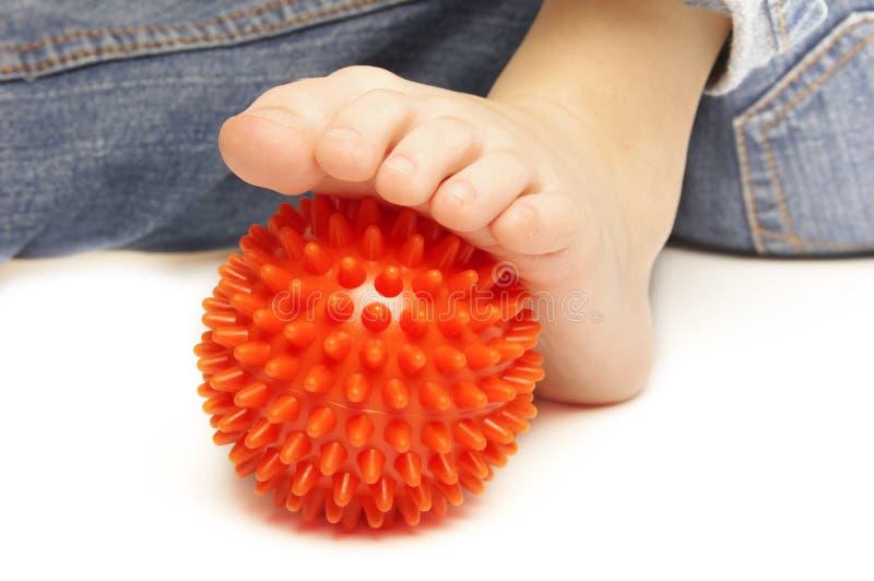Pied d'enfant avec la bille en plastique de massage image libre de droits
