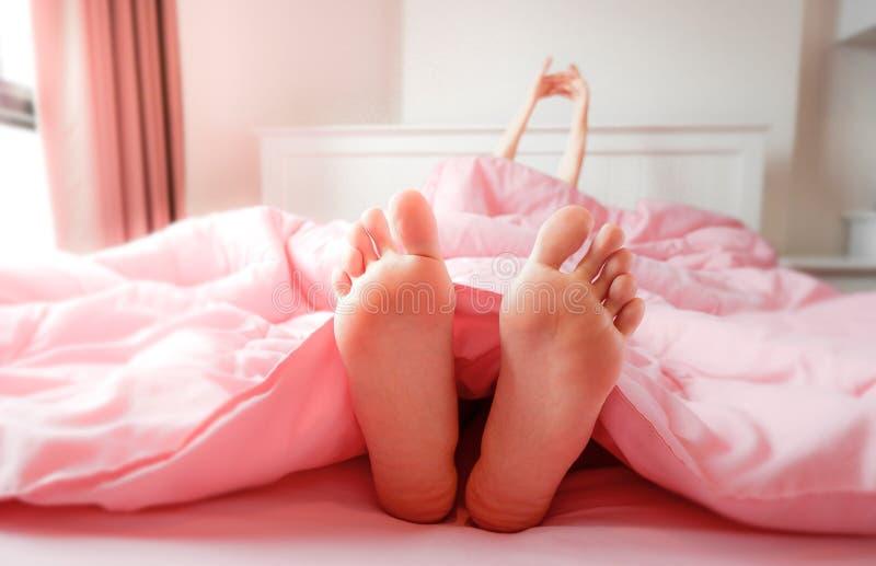 Pied dans le lit ? la maison, dormant et d?tendre Deux pieds sur le lit dans la literie rose Belle jeune femme aux pieds nus dans photographie stock libre de droits