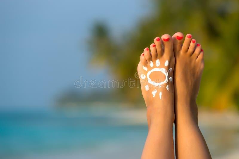 Pied de femme avec de la crème en forme de soleil du soleil dans le conce tropical de plage photos libres de droits