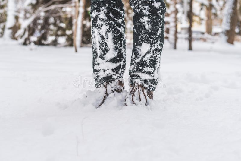 Pied de jambes d'homme dans les bottes chaudes d'hiver marchant dans la neige f photo stock