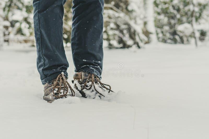Pied de jambes d'homme dans les bottes chaudes d'hiver marchant dans la neige f images stock