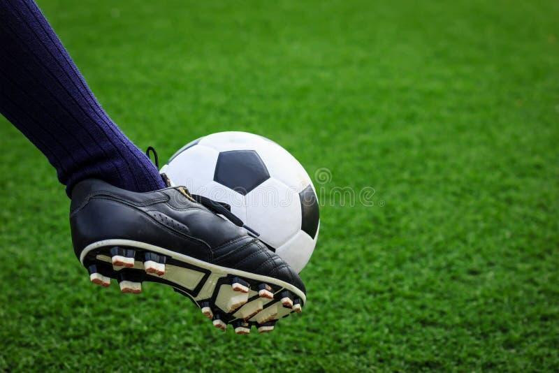 Pied donnant un coup de pied le ballon de football photo libre de droits