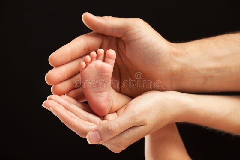 Pied nouveau-né de bébé dans des mains de parents image stock
