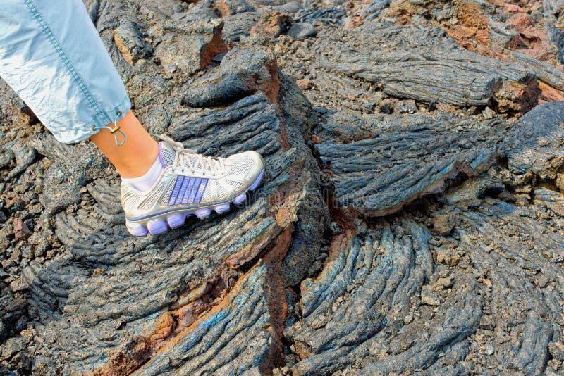 Pied sur les pierres du flux volcanique image libre de droits