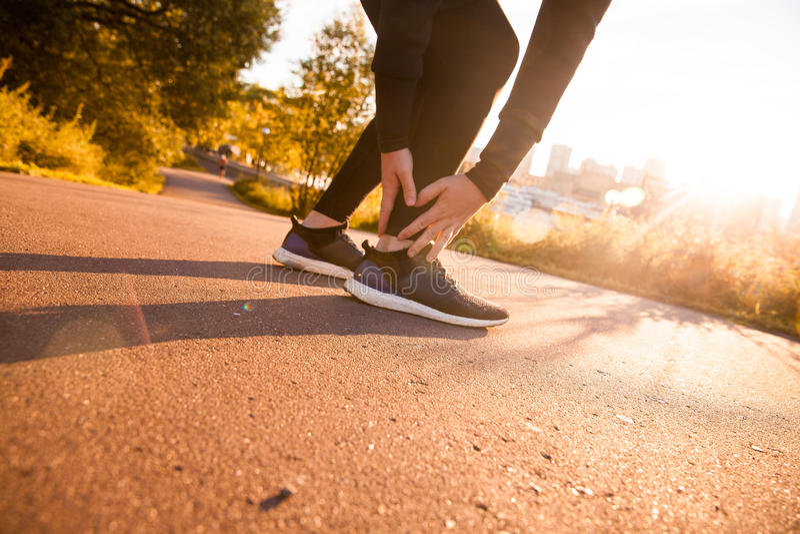 Piede commovente del corridore atletico dell'uomo nel dolore dovuto la caviglia storta fotografie stock libere da diritti