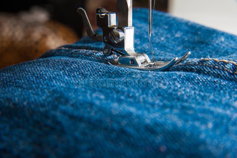 Piede della macchina per cucire sui jeans fotografia stock