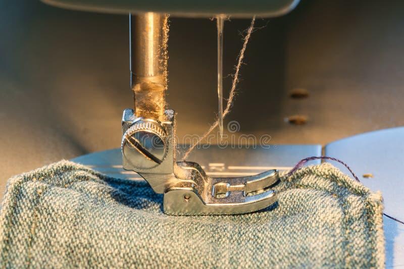 Piede della macchina per cucire sul tessuto dei jeans immagini stock