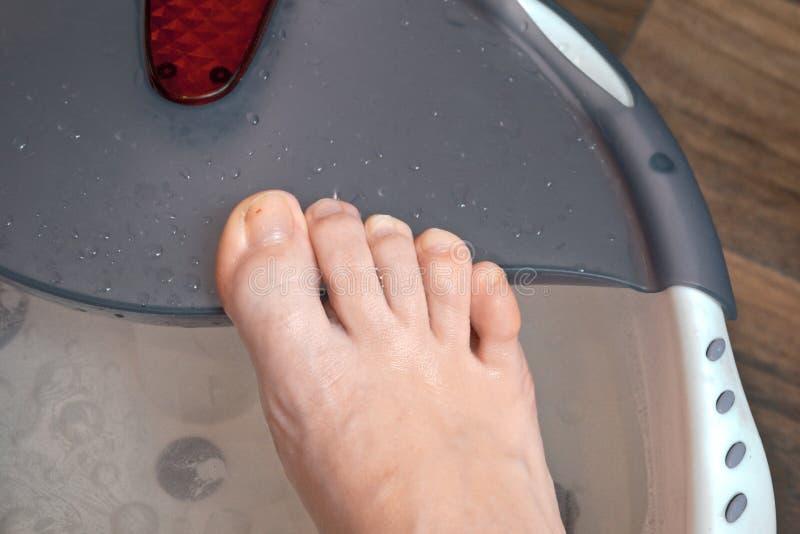 Piede destro che vizia il otmokaet di pedicure in una stazione termale specializzata del piede con effetto di massaggio immagini stock