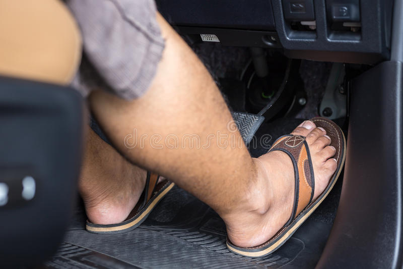 Piede destro con il punto della scarpa di Flip-flop sull'acceleratore nel Mo fotografia stock
