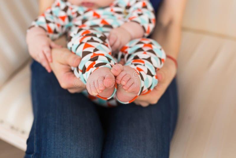 Piede in mani femminili, primo piano del bambino Gamba sveglia del bambino Maternità, amore, cura, nuovo concetto di vita fotografia stock libera da diritti