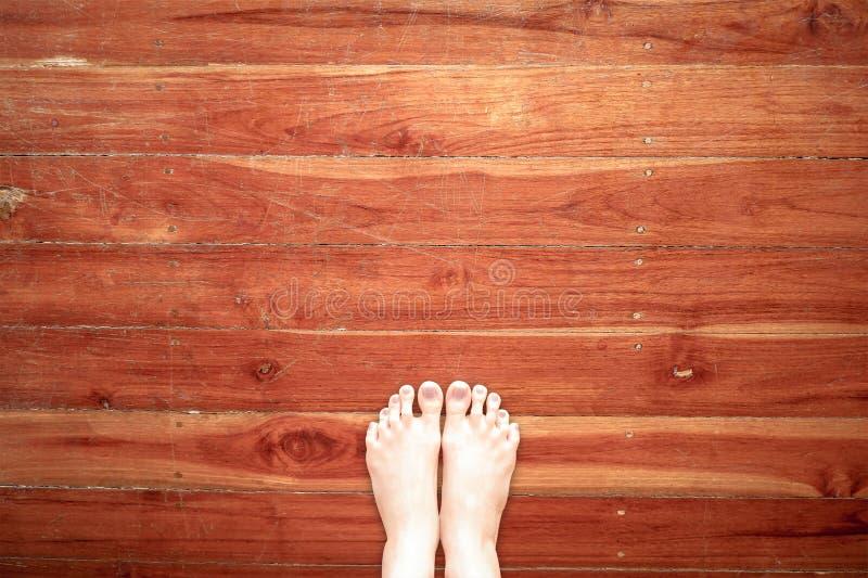 Piede nudo che sta sul fondo di legno del pavimento, vista superiore Selfie dei piedi nudi e della gamba della donna su legno Imm fotografia stock libera da diritti