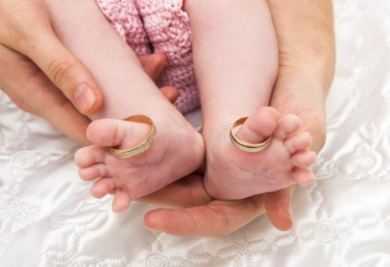Piedi appena nati del bambino in mani della madre immagini stock