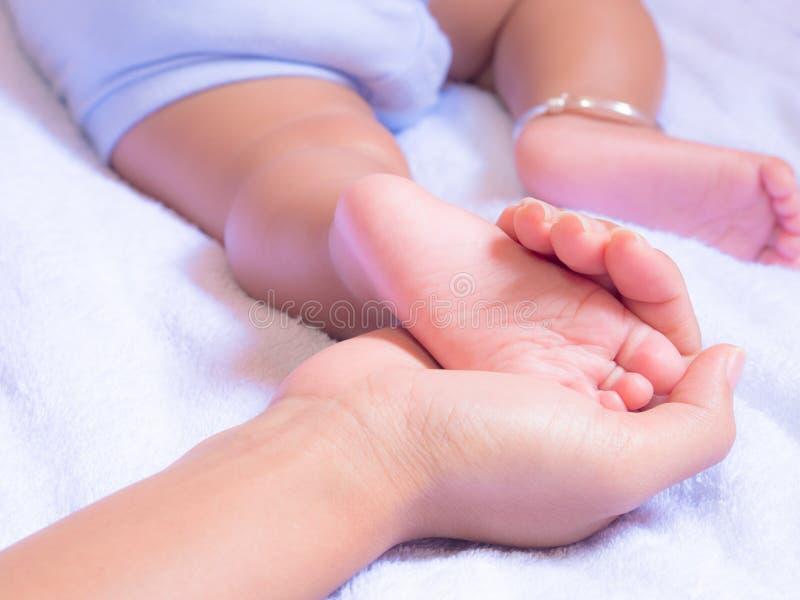 Piedi del bambino in mani della madre immagini stock