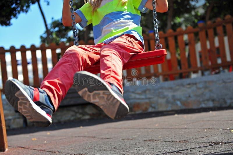 Piedi del bambino su oscillazione al campo da giuoco fotografie stock