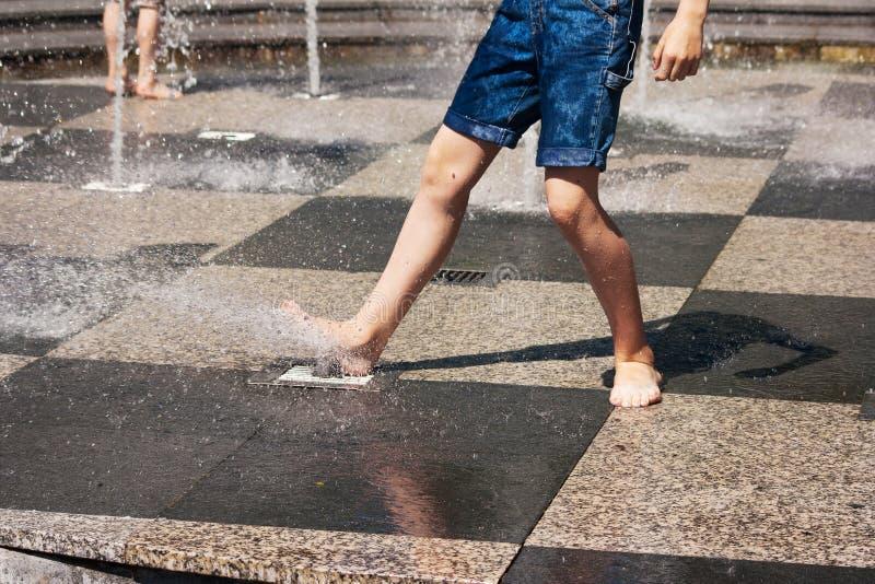 Piedi del ragazzo che giocano nella fontana