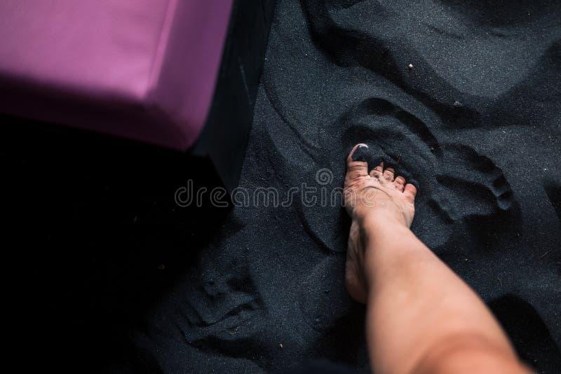 Piedi del ` s della donna sulla sabbia nera da sopra fotografie stock libere da diritti