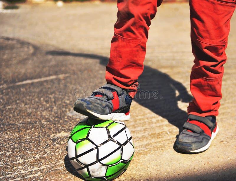 Piedi del ` s del ragazzo con calcio fotografia stock libera da diritti
