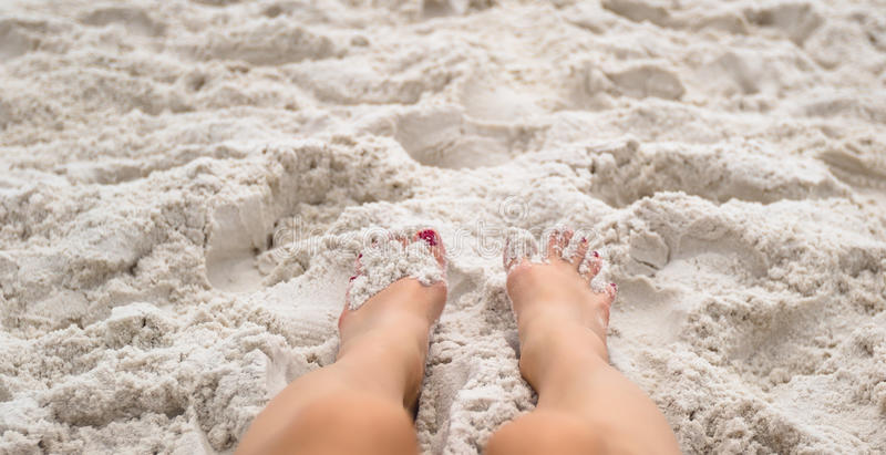 Piedi della donna che mettono sulla spiaggia immagine stock libera da diritti