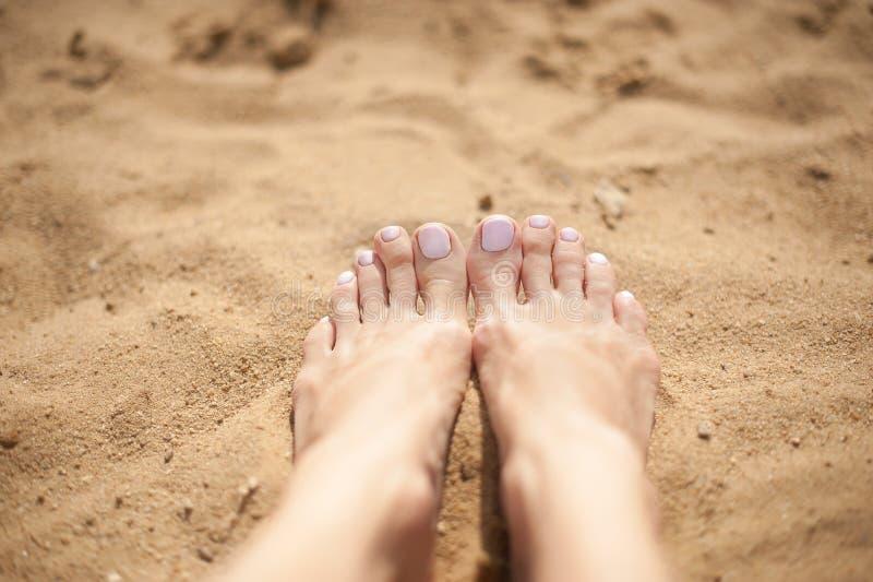 Piedi della donna con le unghie del piede rosa-chiaro sulla sabbia fotografia stock libera da diritti