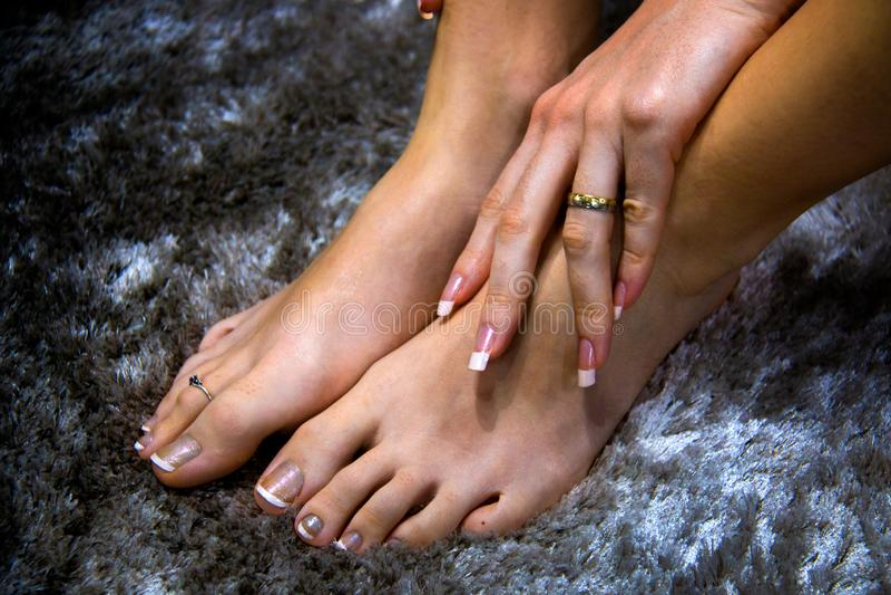 Piedi della donna e mano naturalmente bella, arte elegante ed alla moda morbida sulle unghie, fondo grigio della pelle, del manic immagine stock