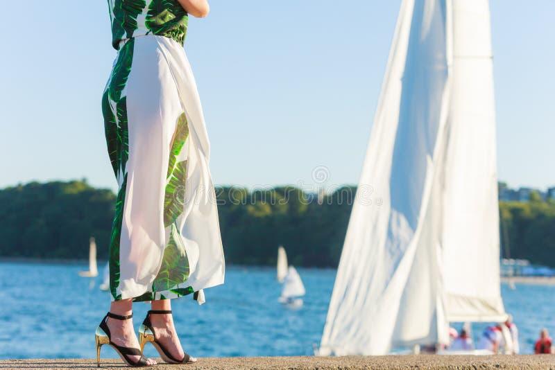 Piedi della donna in scarpe dei tacchi alti sul pilastro del mare immagini stock libere da diritti