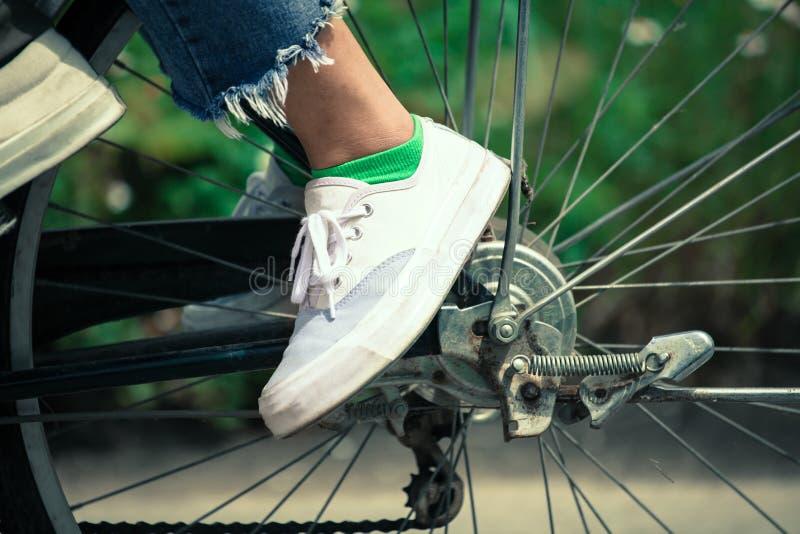 Piedi della giovane donna che guidano una bicicletta immagini stock libere da diritti