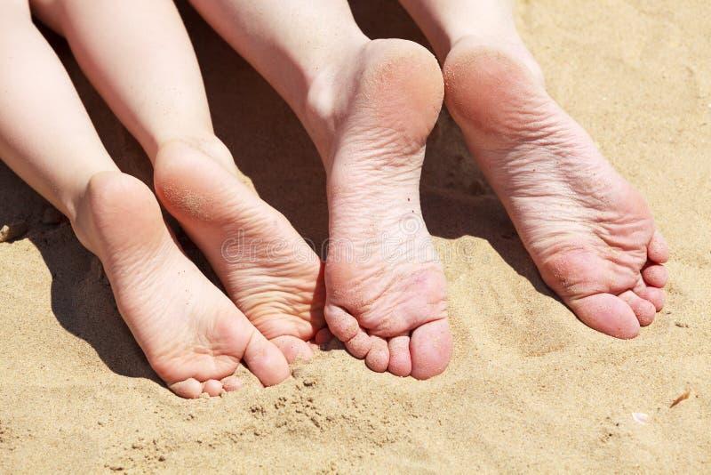 Piedi della madre e del suo bambino nella sabbia fotografia stock libera da diritti
