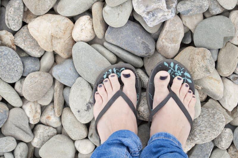 Piedi della ragazza in sandali, con smalto blu sulla spiaggia rocciosa immagine stock
