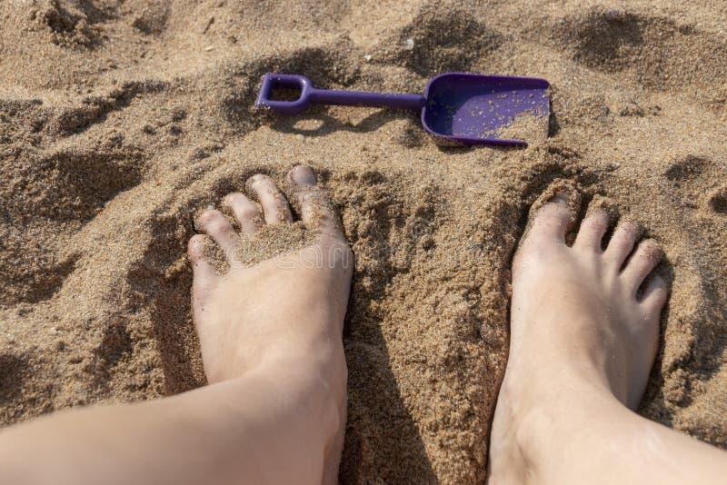 Piedi delle persone nella sabbia fotografia stock