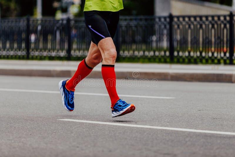 piedi di corridore dell'uomo nei calzini rossi di compressione immagini stock libere da diritti