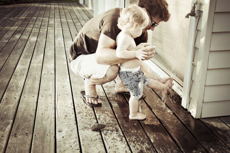 Piedi di lavaggio del padre del figlio immagini stock libere da diritti