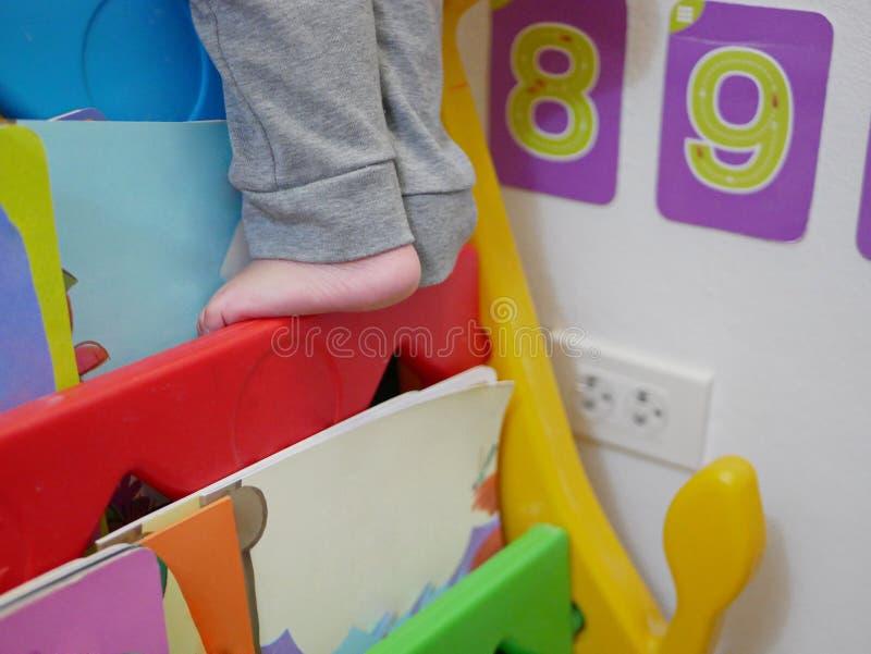 Piedi di piccolo bambino che scala e che fa un passo sugli scaffali di libro immagini stock