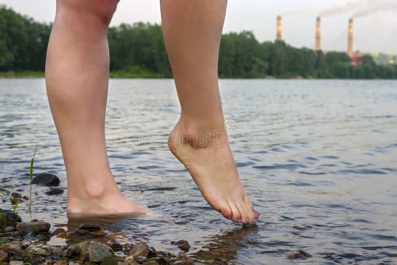 Piedi di ragazza nel fiume sui precedenti dei tubi della fabbrica producendo fumo fotografia stock libera da diritti