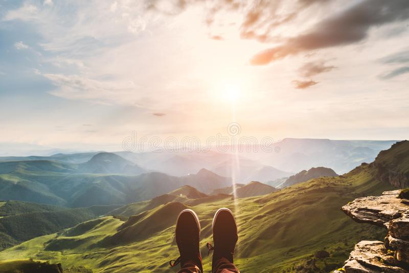 Piedi di Selfie dei pantaloni a vita bassa di viaggiatore delle scarpe che si rilassa sulle montagne della scogliera all'aperto c immagini stock