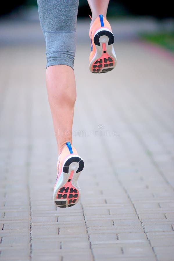 Piedi di un funzionamento dell'atleta su un addestramento di via del parco per i fitnes fotografia stock