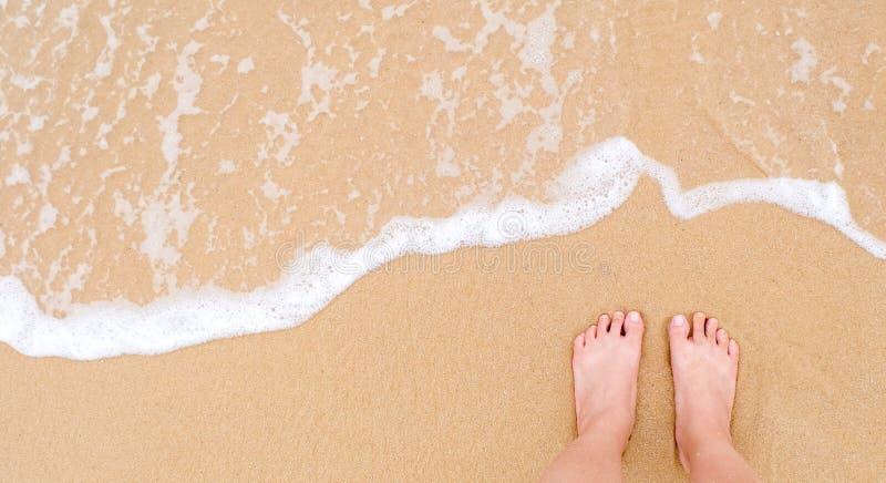 Piedi di una donna sulla spiaggia sabbiosa fotografia stock