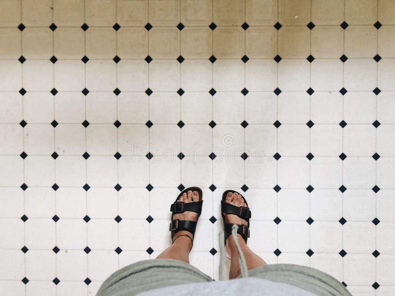 Piedi di una persona in sandali sulle mattonelle bianche in un bagno fotografia stock libera da diritti